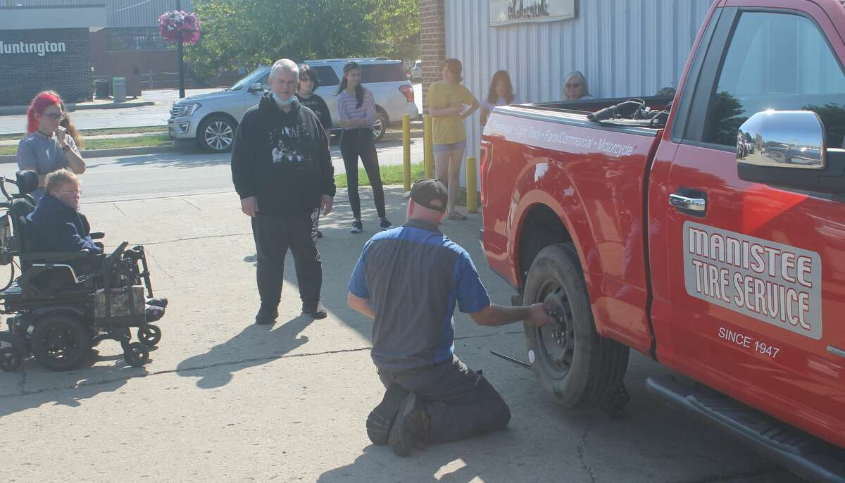 Nate Miller, owner of Manistee Tire, puts on lug nuts to secure the spare tire to his trucking during a demonstration for the Manistee Friendship Society Thursday morning.