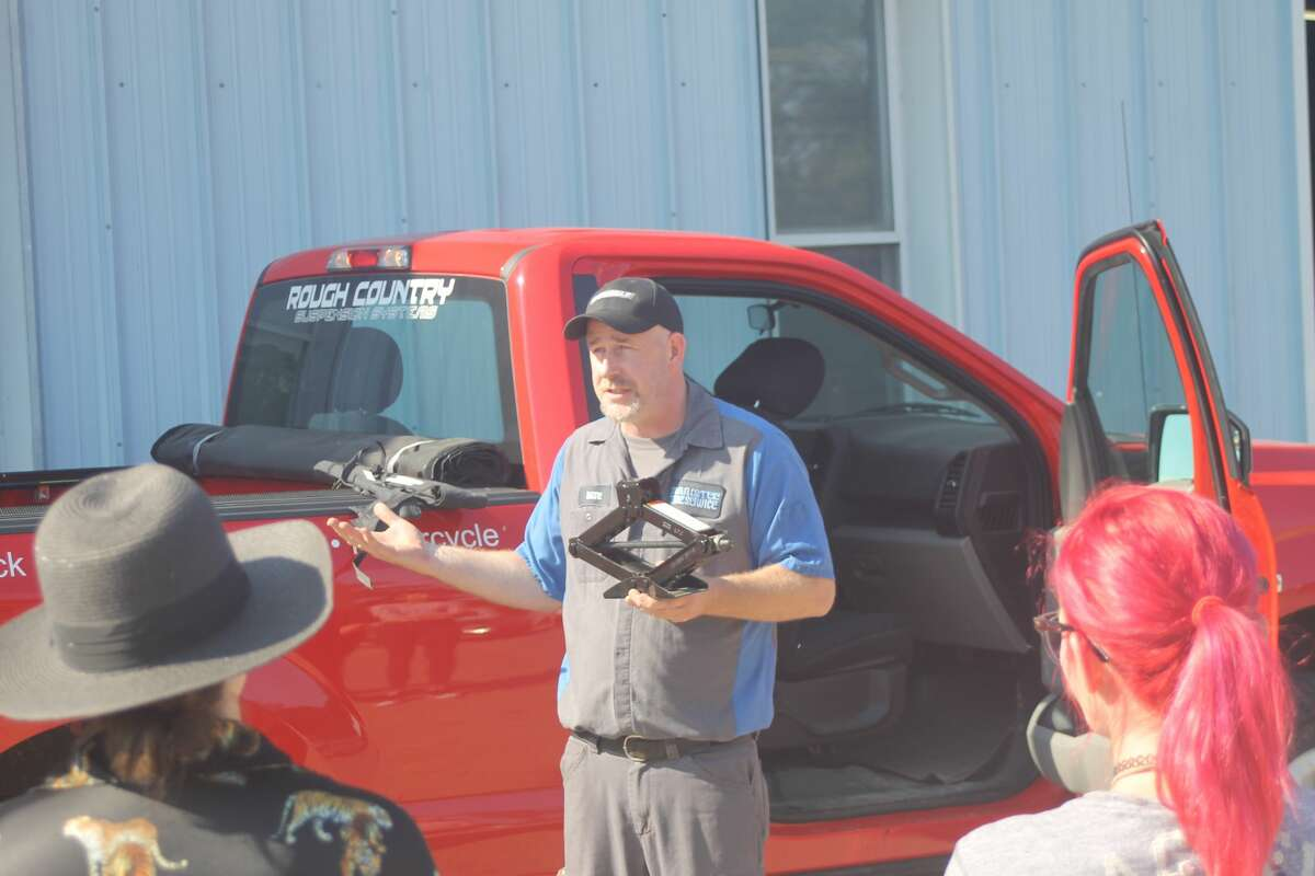 Nate Miller, owner of Manistee Tire, explains how to use a jack while teaching Manistee Friendship Society members and friends how to change a flat tire.