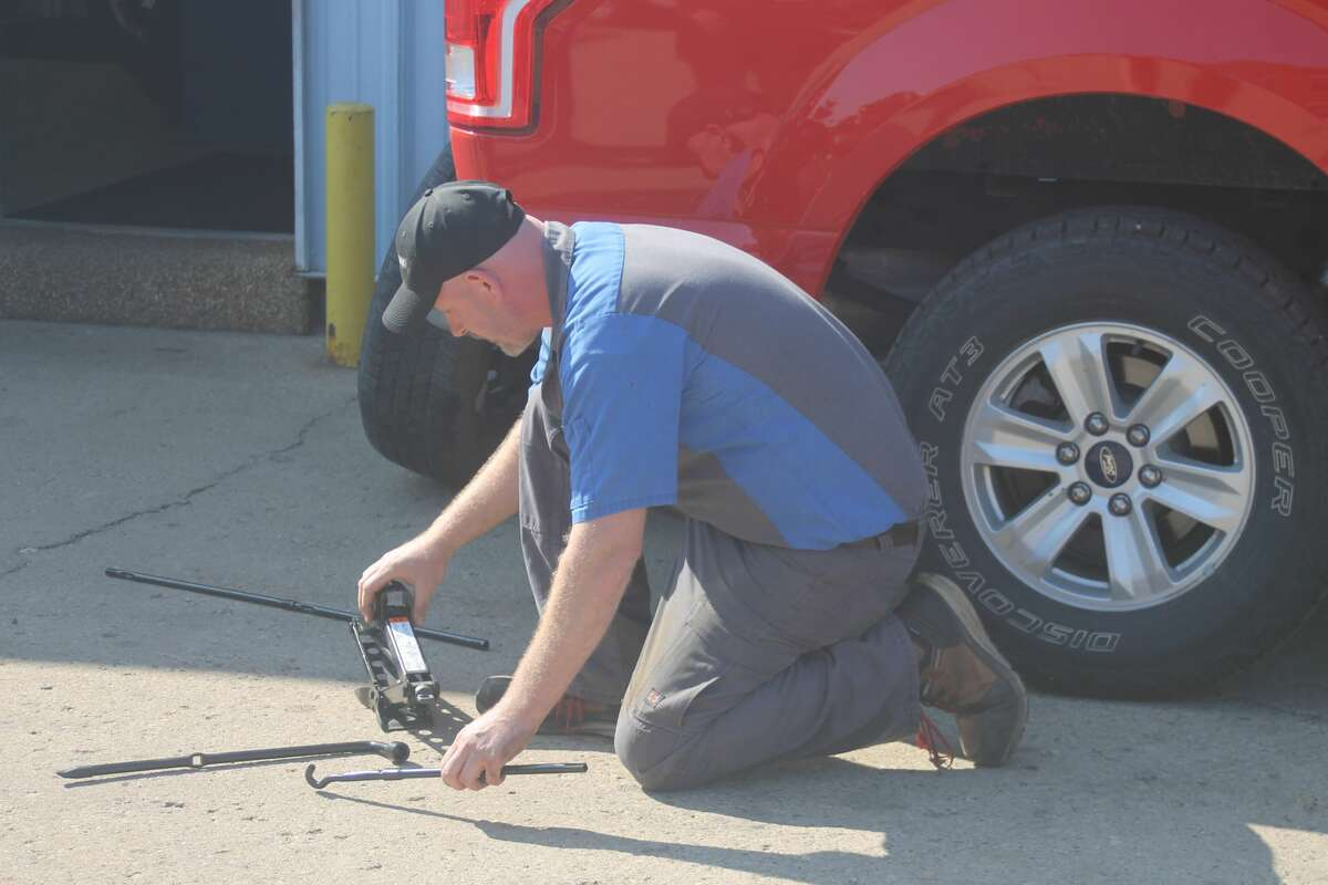 Manistee Tire owner Nate Miller conducts a tire changing demonstration for the Manistee Friendship Society on Thursday morning.
