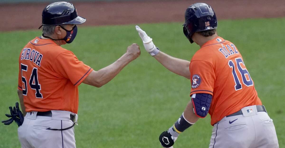 Houston Astros' Aledmys Diaz (16) celebrates with first base coach Dan Firova (54) after hitting an RBI single during the tenth inning of a baseball game against the Kansas City Royals Thursday, Aug. 19, 2021, in Kansas City, Mo. The Astros won 6-3 in ten innings. (AP Photo/Charlie Riedel)