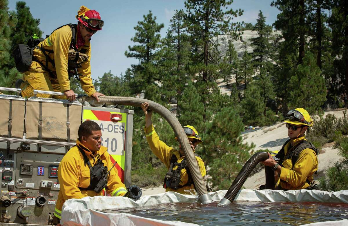 Firefighters fill a truck using water from a reserve pool near Janesville (Lassen County) on Thursday.