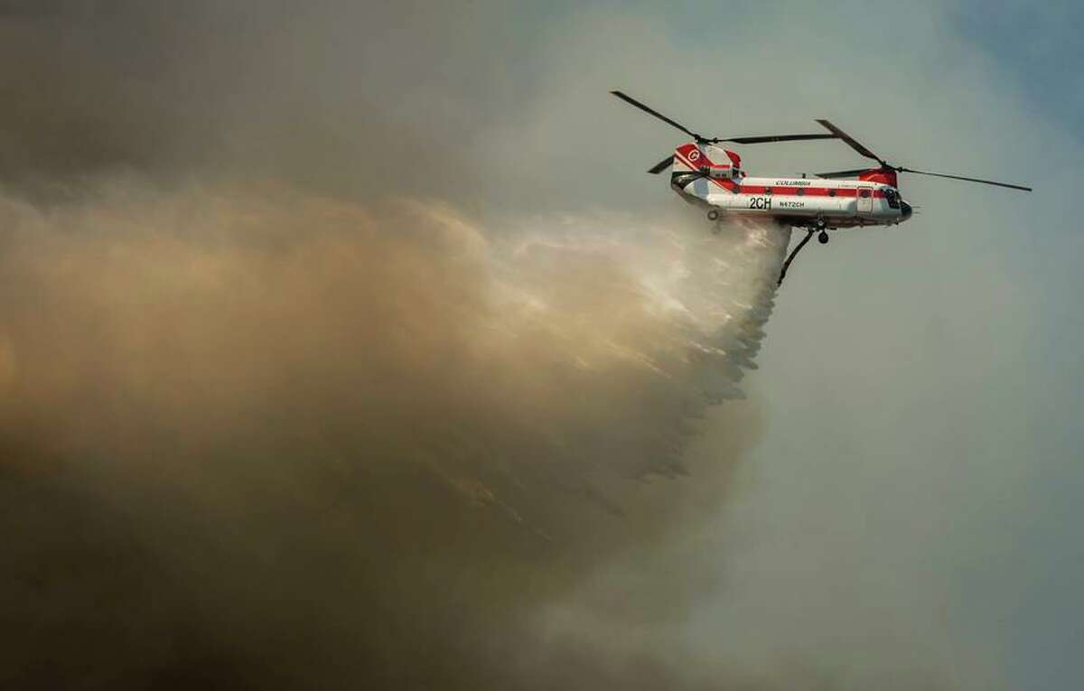 A plane drops water on a growing blaze near Janesville on Thursday. The Dixie Fire is the largest wildfire in the United States and has burned more than 700,000 acres.