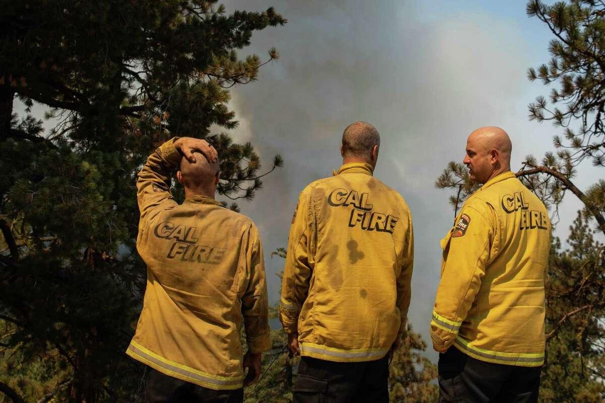 Firefighters observe a growing blaze from Janesville Grade Road near Janesville (Lassen County) on Thursday.