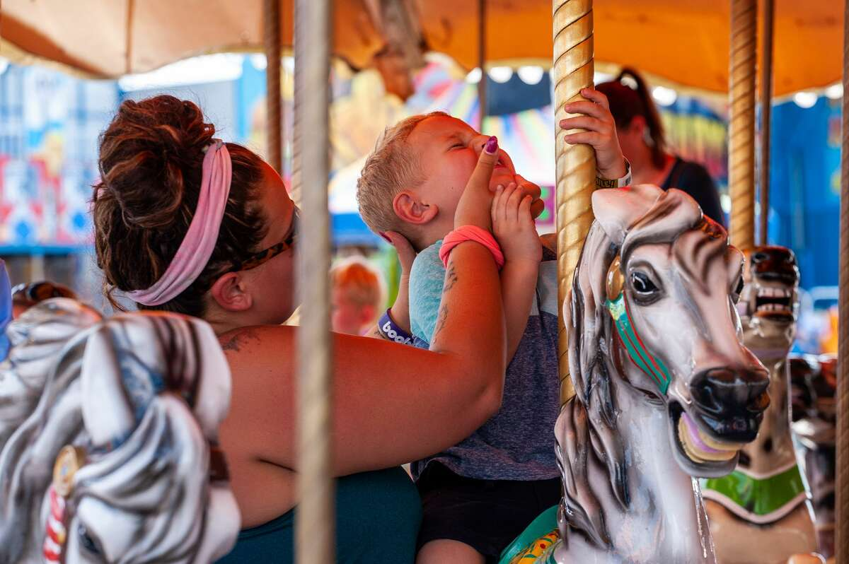 People gaze at animals and enjoy carnival rides on Thursday, Aug. 19, 2021 at the Midland County Fair.