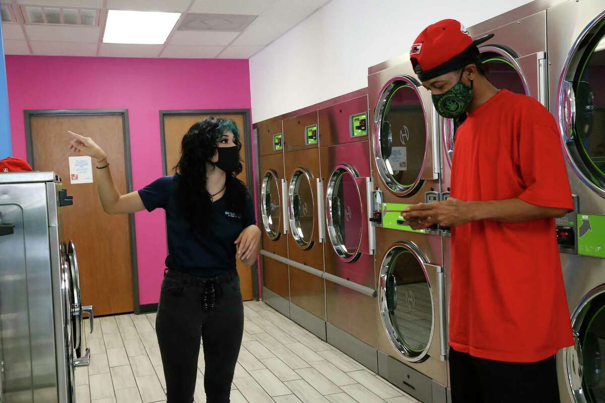 BiblioTech outreach worker Araceli Linares, left, hands out information on their programs to Thomas Pate, who was doing his laundry at Laundry Rey's on South New Braunfels Avenue on Thursday. Libraries Without Borders has partnered with BiblioTech, San Antonio Public Library and Google Fiber to deliver Wi-Fi hotspots and internet access to hundreds of San Antonio residents through the nonprofit's Wash and Learn Initiative that equips laundromats with computers and in-person programs.