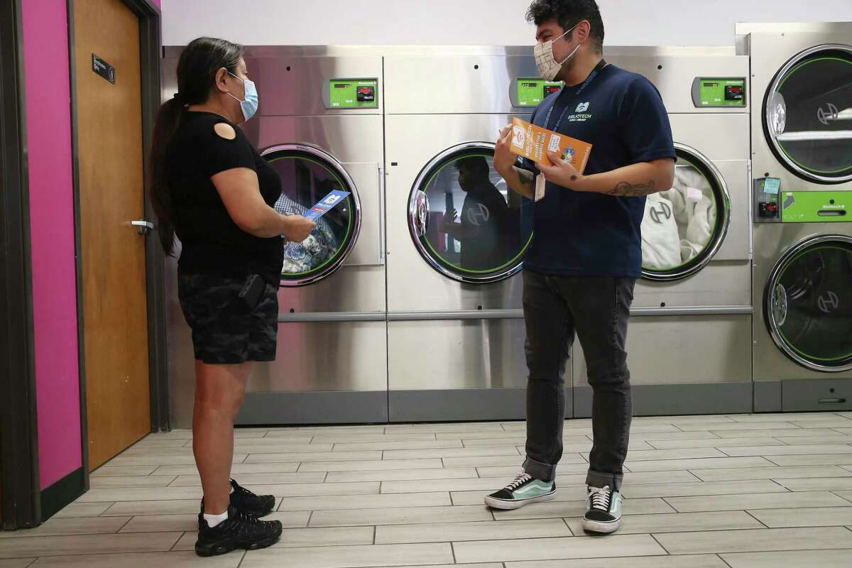 BiblioTech outreach worker Jassiel Gomez, right, hands out information on their programs to Bertha Celestino, who was doing her laundry at Laundry Rey's on South New Braunfels Avenue on Thursday. Libraries Without Borders has partnered with BiblioTech, San Antonio Public Library and Google Fiber to deliver Wi-Fi hotspots and internet access to hundreds of San Antonio residents through the nonprofit's Wash and Learn Initiative that equips laundromats with computers and in-person programs.