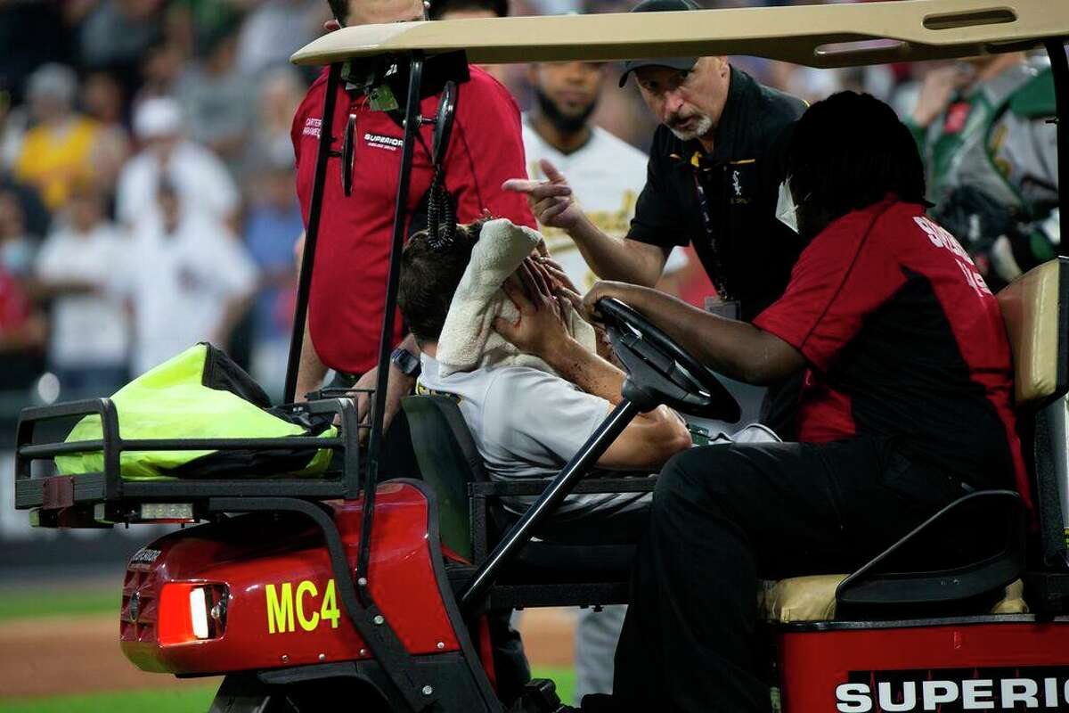 Oakland Athletics starter Chris Bassitt holds a towel to his face as he is removed from the field by medical personnel after getting hit by a line drive from Chicago White Sox left fielder Brian Goodwin during the second inning at Guaranteed Rate Field on Tuesday, August 17, 2021 in Chicago. (Erin Hooley/Chicago Tribune/TNS)