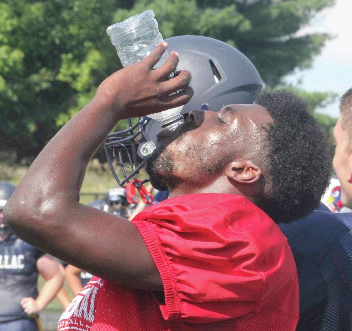 Big Rapids' Jamal Strickland drinks some water during a break at Cardinal Stadium during Thursday's scrimmage. (Pioneer photo/John Raffel)
