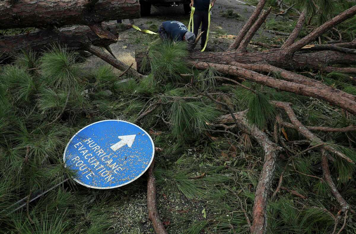 Men work to clear a downed tree blocking a road in Grand Lake after Hurricane Laura struck. Laura went from a Category 1 to Category 4 hurricane in 24 hours, an example of rapid intensification of tropical cyclones that scientists say has likely happened more often.