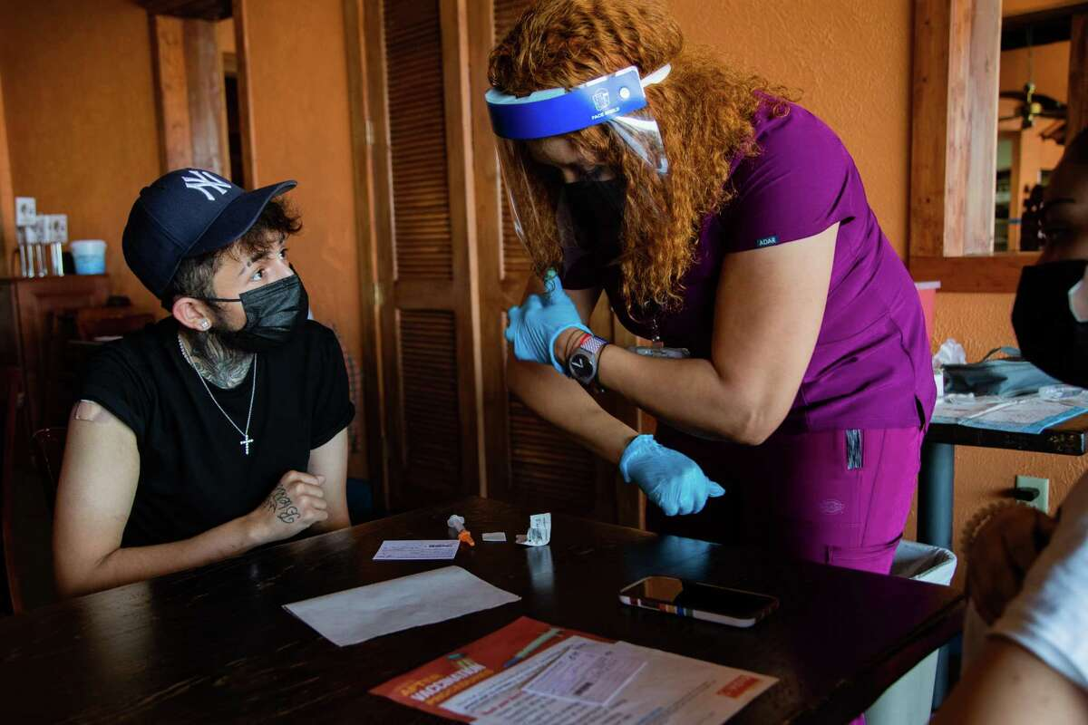 Jose Madrigal, left, 23, receives information about the Moderna COVID-19 vaccine from Harris County Public Health registered nurse Cynthia Orji at a Harris County Public Health vaccination site in the Mi Pueblito Restaurant, Thursday, Aug. 19, 2021, in Houston.