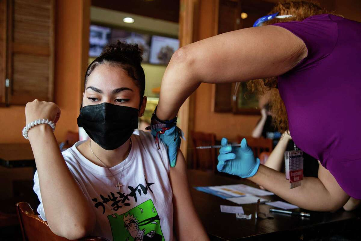 Destiny Charriez, 20, waits to get the COVID-19 Moderna vaccine by Harris County Public Health registered nurse Cynthia Orji at a Harris County Public Health vaccination site in the Mi Pueblito Restaurant, Thursday, Aug. 19, 2021, in Houston.