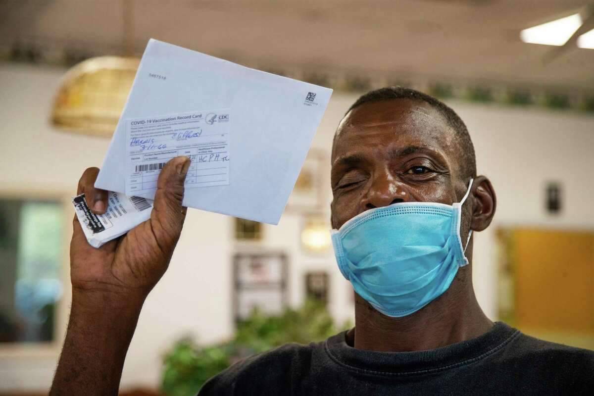 Clifford Harris proudly holds his COVID-19 vaccination card after receiving an inoculation at a Harris County Public Health vaccination site in Dodo's Chicken, Thursday, Aug. 19, 2021, in Houston.