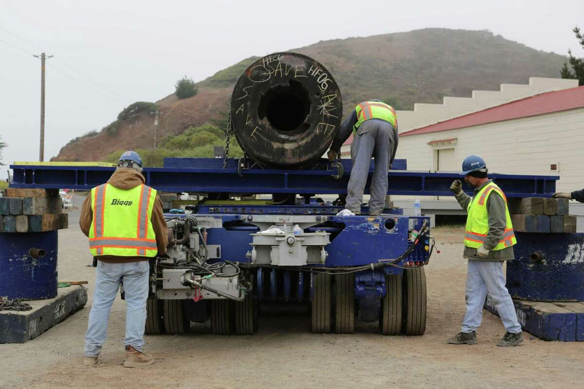Trailer technician Tom Trent (left), Glen Amant and Ron Rabello help secure a gun from the battleship Missouri to a truck for its trip to Battery Townsley in the Marin Headlands in 2012.