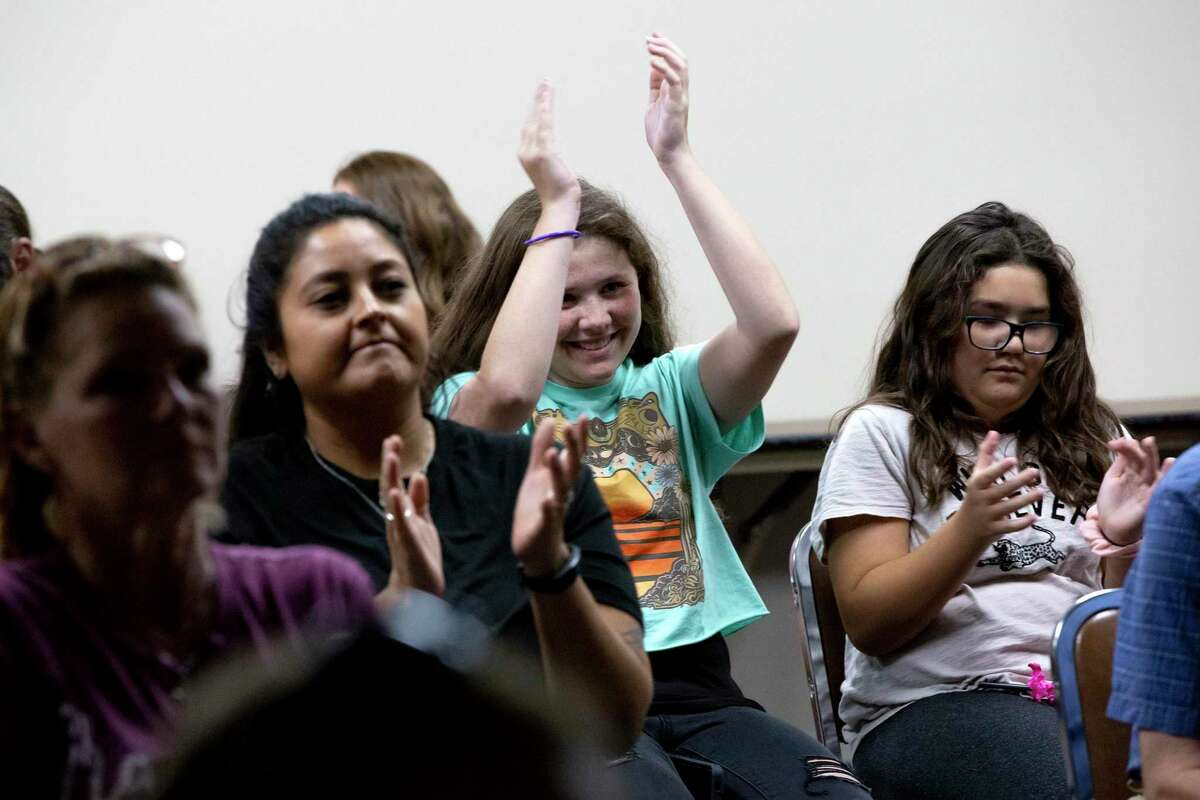 Parents react in an overflow room during an emergency NEISD board meeting Thursday as others speak against a mask mandate in district schools.