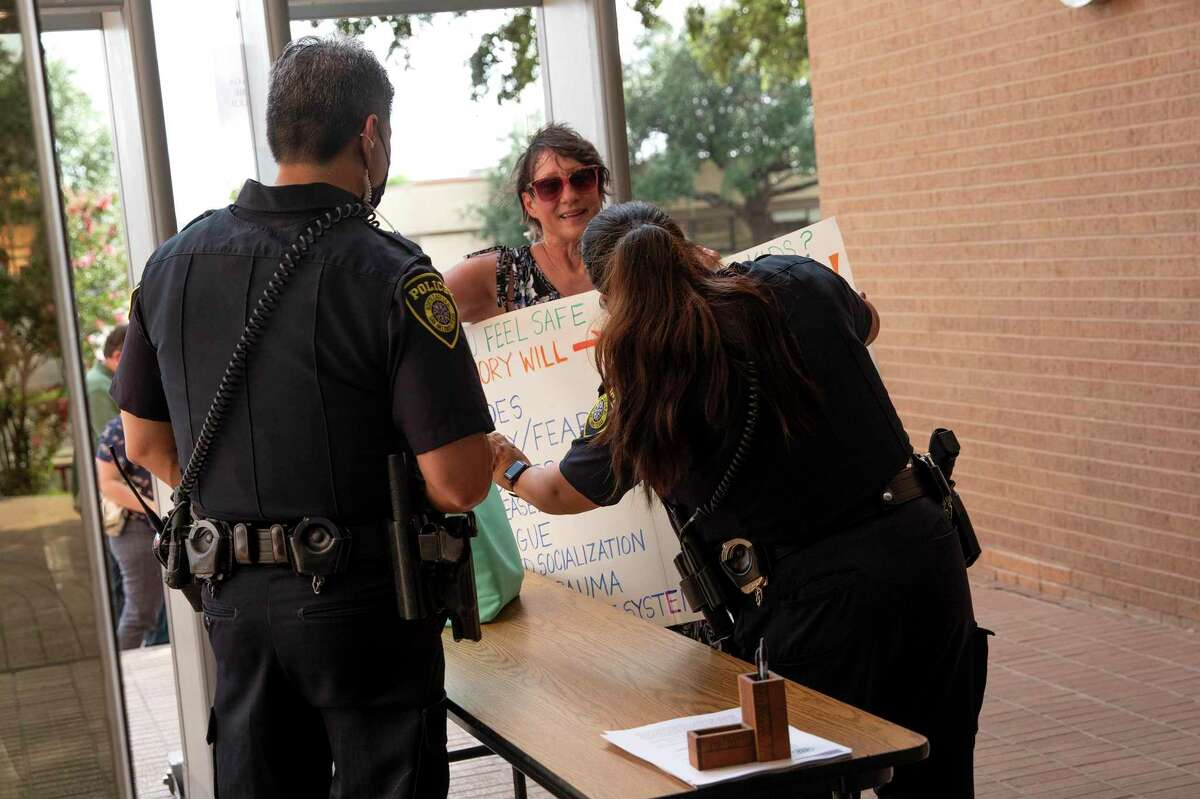 A police officer reads a sign brought to Thursday's NEISD board meeting by an opponent of mandatory mask-wearing in schools.