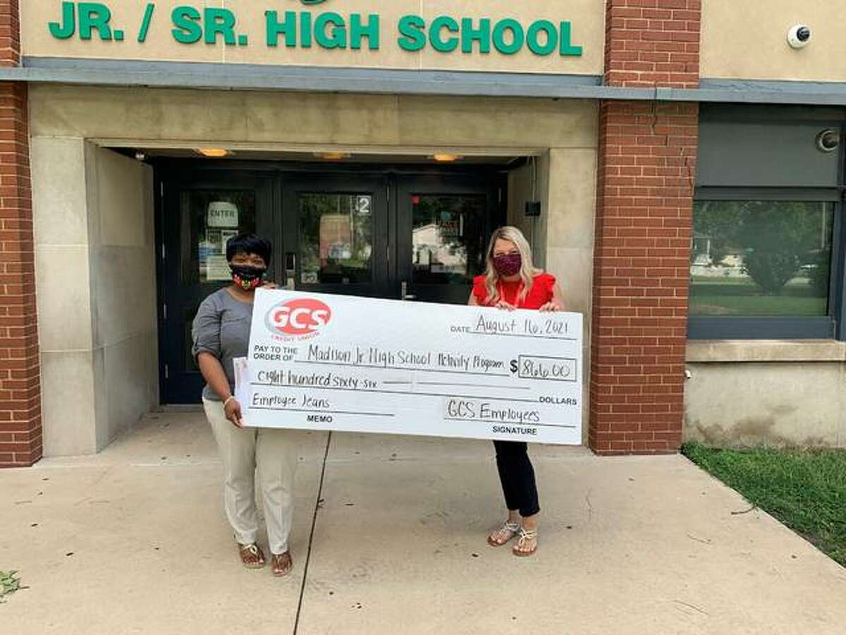 GCS Credit Union employees hold a display check showing their support for Madison Junior High School through their Growing Community Schools Jean Program. Employees donated $866 to the school's Activity Program.
