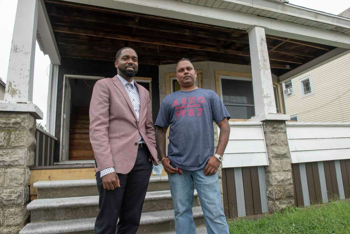Maurice A. Brown III, city of Schenectady's home ownership coordinator, left, stands with Deepnarayan Jealall, first-time homebuyer, in front of the home Jealall is renovating on Thursday, Aug. 19, 2021 in Schenectady, N.Y.