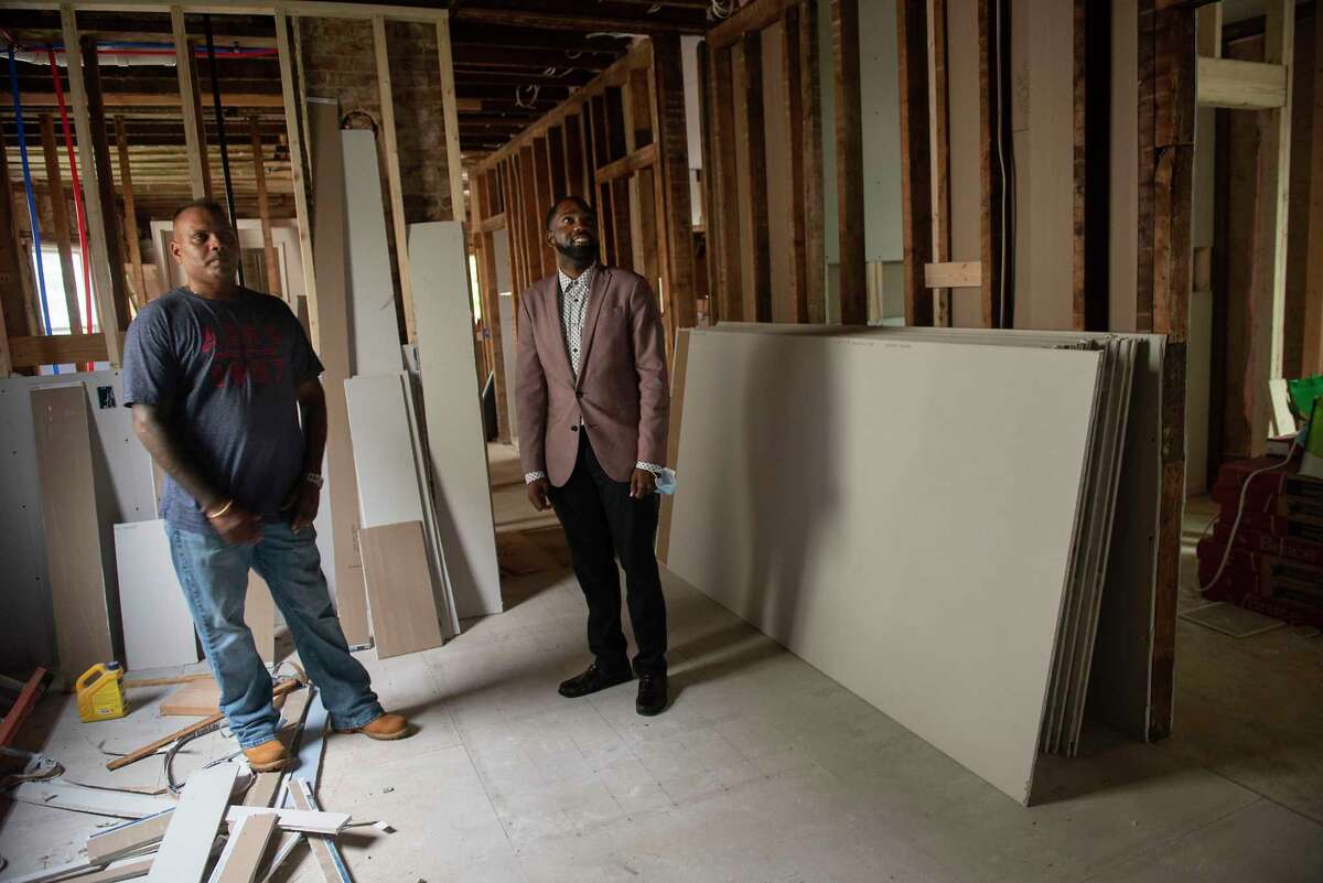 Deepnarayan Jealall, first-time homebuyer, left, shows Maurice A. Brown III, city of Schenectady's home ownership coordinator, the home he is renovating on Thursday, Aug. 19, 2021 in Schenectady, N.Y.