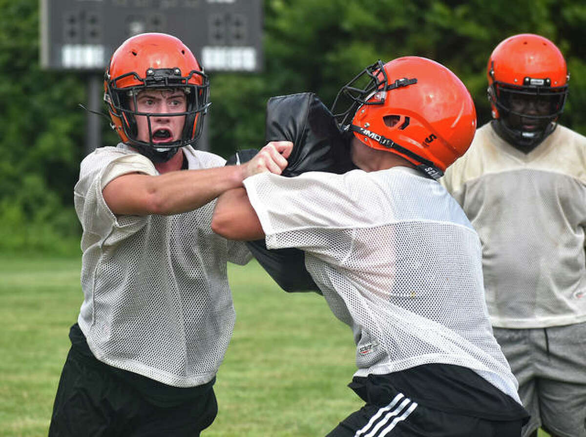 The Edwardsville Tigers run through drills during a preseason practice inside the District 7 Sports Complex.