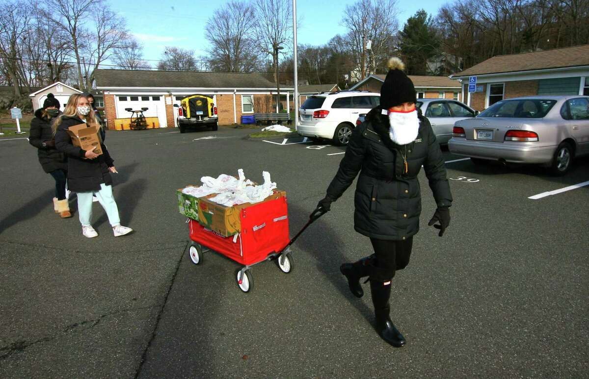 New American Dream Foundation Vice President Emanuela Palmares arrives with volunteers to deliver meals to senior citizens at Glen Apartments in Danbury, Conn., on Saturday Dec. 26, 2020. Ticket sales from the gala benefit the meals program.