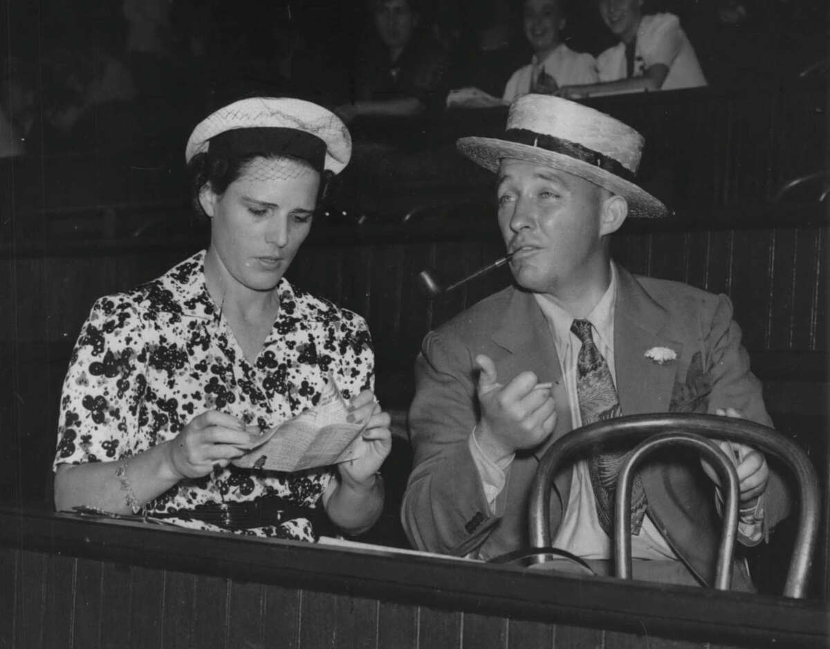 New York - Bing Crosby and his hostess, Mrs. C. S. Howard of San Francisco, are shown discussing the nags from the standpoint of owners as they attend the races at Saratoga Springs, New York. Mrs. Howard is owner of Seabiscuit. Bing arrived at Saratoga Springs August 19, planning to spend a week at the resort. August 20, 1937 (Times Union Archive)