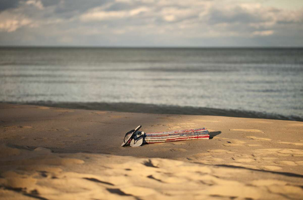 Flip flops and mat sitting on a lake beach in Oscoda County.