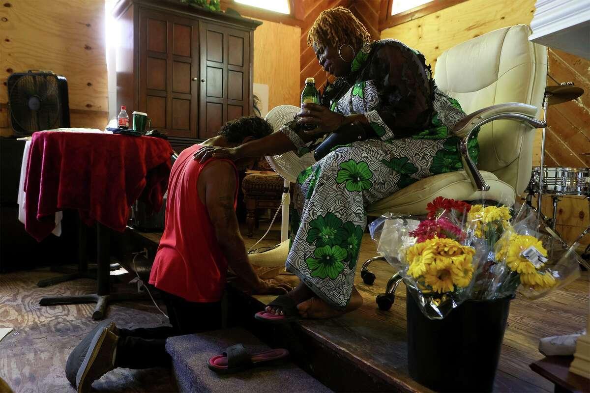 Pastor Shetigho Nakpodia of Redeemer's Praise Church prays for Alex Menuzo, 50.