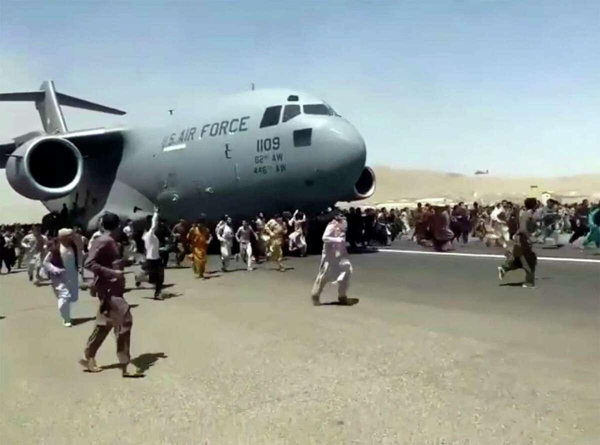 Hundreds of people run alongside a U.S. Air Force C-17 transport plane as it moves down a runway of the international airport, in Kabul, Afghanistan. They are helping to flee the Taliban.