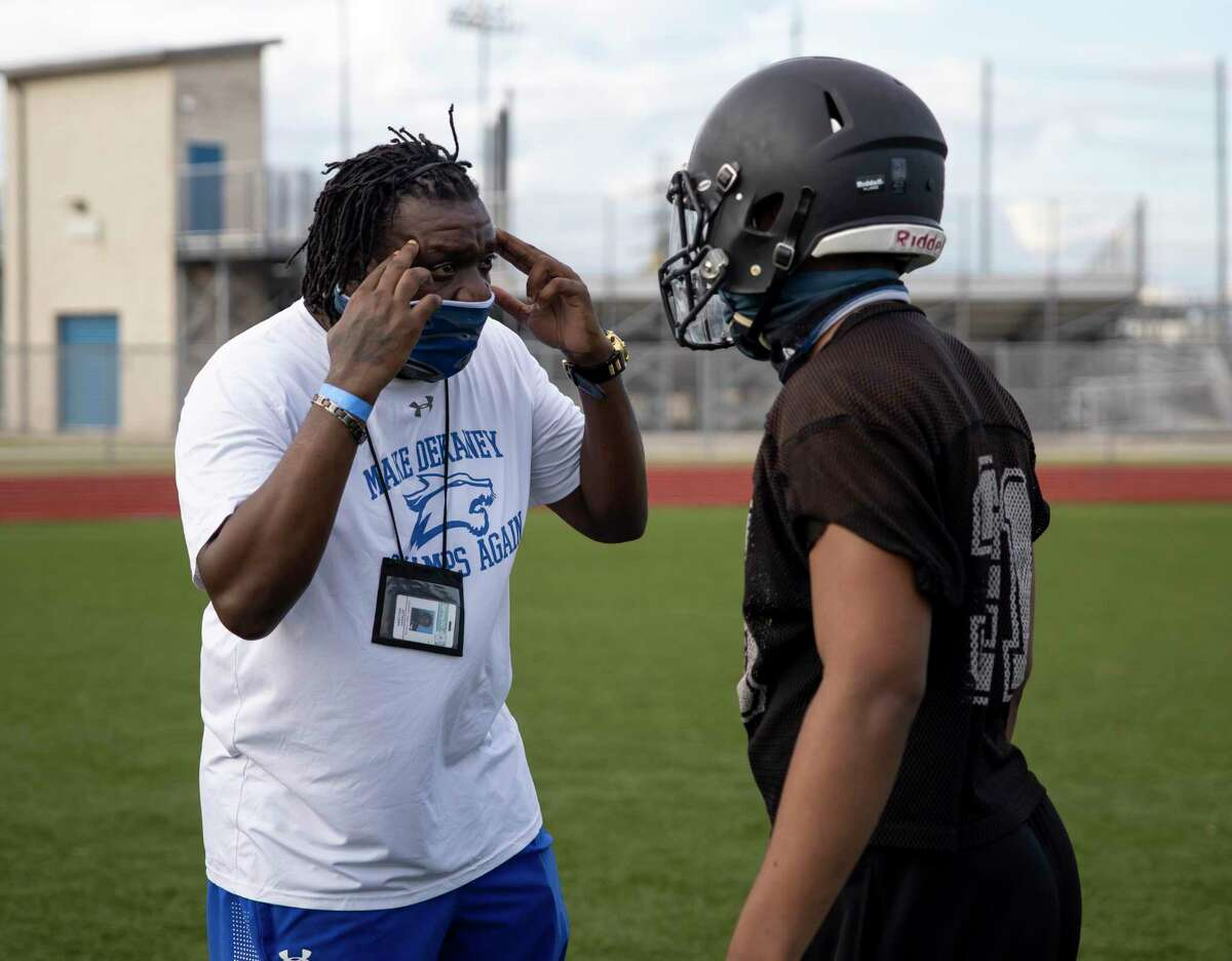 Coach Anthony Williams talks with a player during football practice held at Dekaney High School in Houston, Thursday, Sept. 17, 2020.