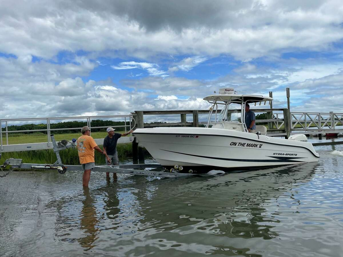 From left, as Tom Markiewicz steers the boat, Cliff Johnson and James Catlin guide him onto the trailer at the Guilford Boat Launch to get his boat out before Tropical Storm Henri descends.