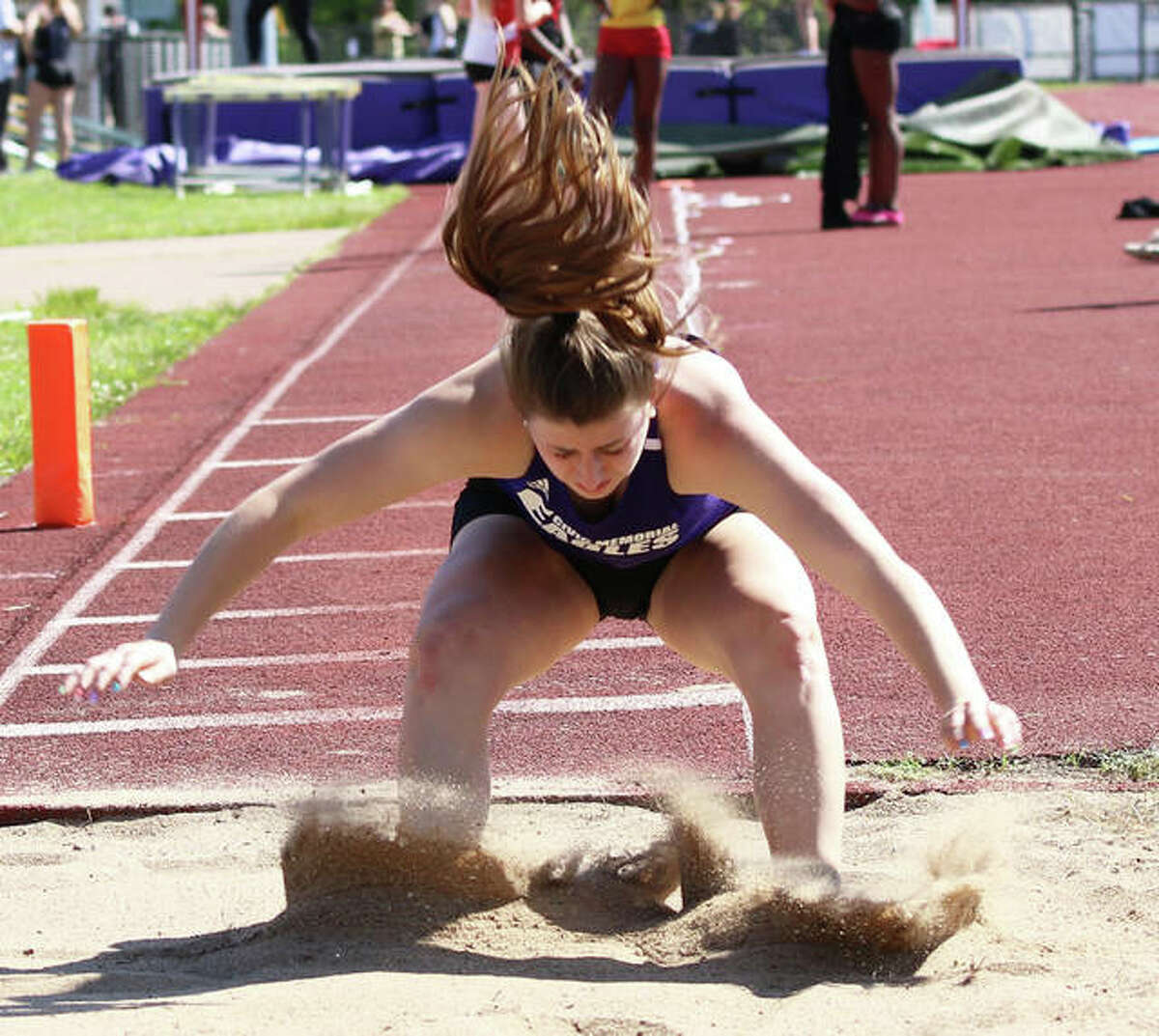 CM grad Jackie Woelfel, shown during long jump competition for the Eagles track team, signed with Kansas Jayhawks rowing earlier this year and will begin fall workouts, along with classes, Monday in Lawrence.