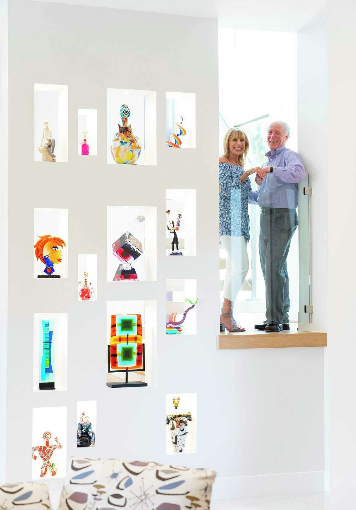 Shelly and Steve Strauss pose for a photo on the landing of their staircase, adjacent to a wall with art niches displaying some of their art glass collection.