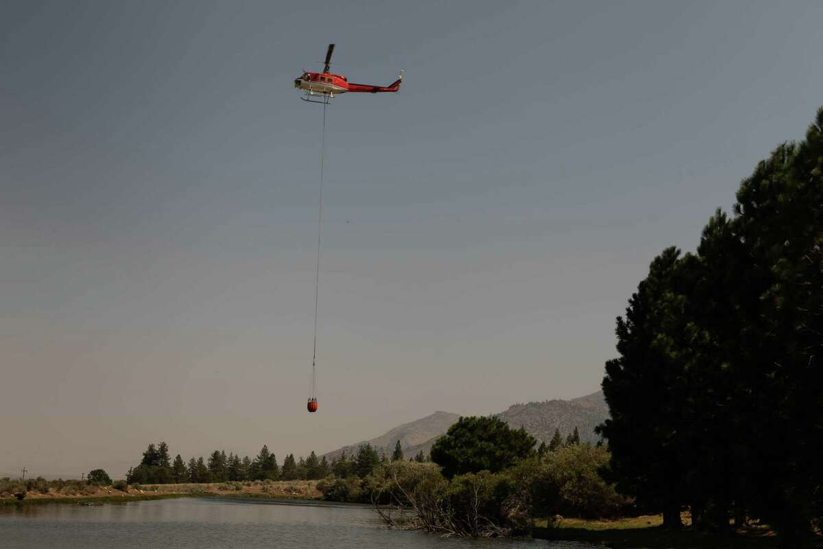 A helicopter gathers water from a farmer's pond and carries it toward the Dixie Fire burning north of Milford on Wednesday.