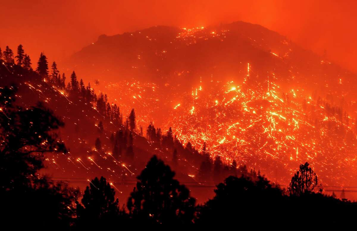 Seen in a long-exposure photograph, embers light up hillsides as the Dixie Fire burns near Milford (Lassen County) on Tuesday.