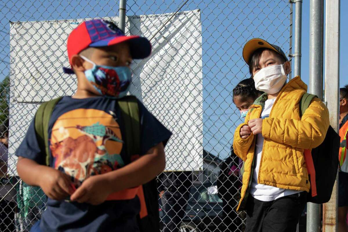 Students wear masks as they arrive for their third day of full, in-person learning at Garfield Elementary School on Wednesday, August 11, in Oakland, Calif.