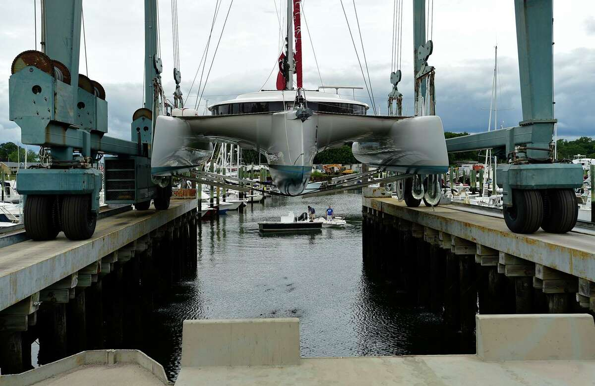 Workers at Cove Marina remove boats from the water including the Predominance ahead of Hurricane Henri Friday, August 20, 2021, in Norwalk, Conn.