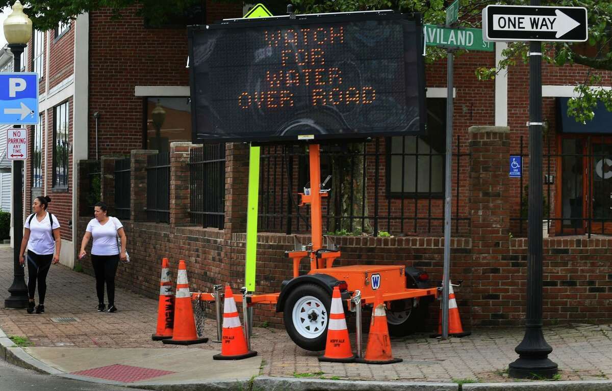 A sign on Water Street warns residents of rising water ahead of Hurricane Henri Friday, August 20, 2021, in Norwalk, Conn.
