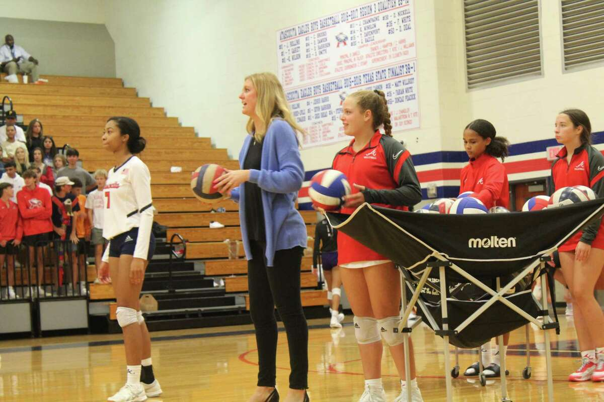 The Atascocita Lady Eagles warmup under the watchful eye of first year volleyball coach Madeline Odom (in the blue coat).