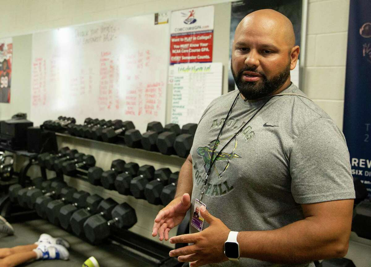Sharpstown High School Football Head Coach Cirilo Ojeda Jr. talks to players at the beginning of a training session with strength and conditioning coach Aislinn Garza, not in photo, Wednesday, Aug. 4, 2021, in Houston. Garza is the only female strength and conditioning coach in Houston.