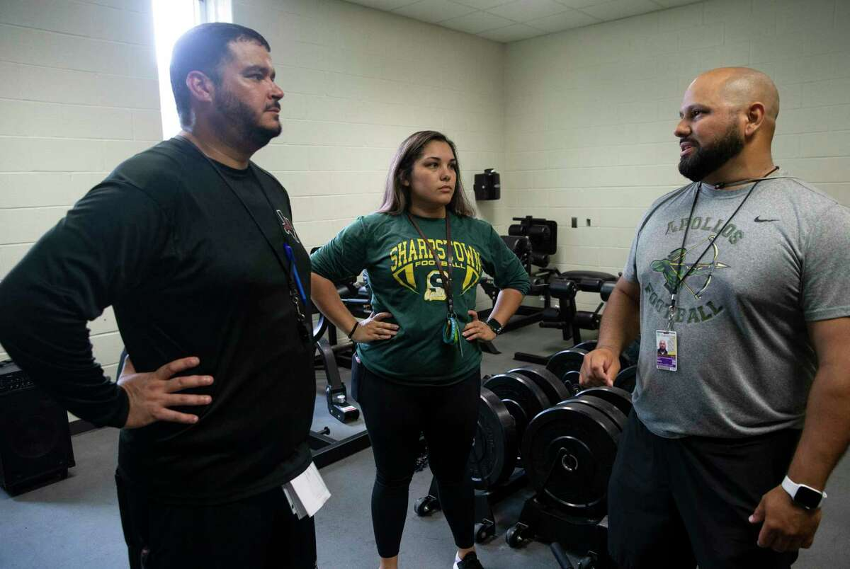 Sharpstown High School Football Head Coach Cirilo Ojeda Jr., far right, has a conversation with strength and conditioning coach Aislinn Garza and offensive coordinator Matthew Torres during a training session Wednesday, Aug. 4, 2021, in Houston. Garza is the only female strength and conditioning coach in Houston.