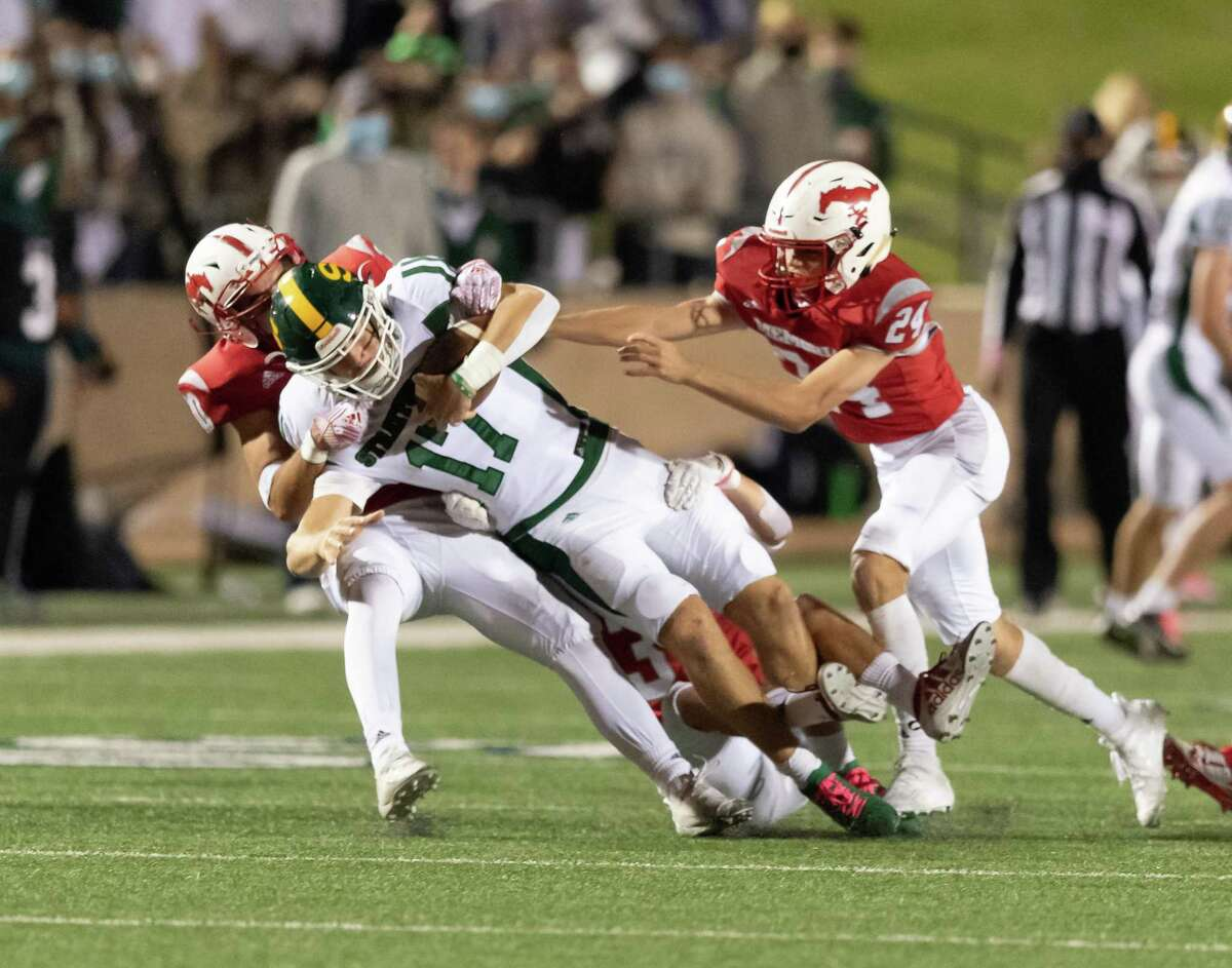 AJ Abbott (17) of the Stratford Spartans is brought down by Bauer Bruce (30) and Carter Wienert (24) of the Memorial Mustangs in the second half during a High School football game on Friday, October 30, 2020 at Tully Stadium in Houston Texas.