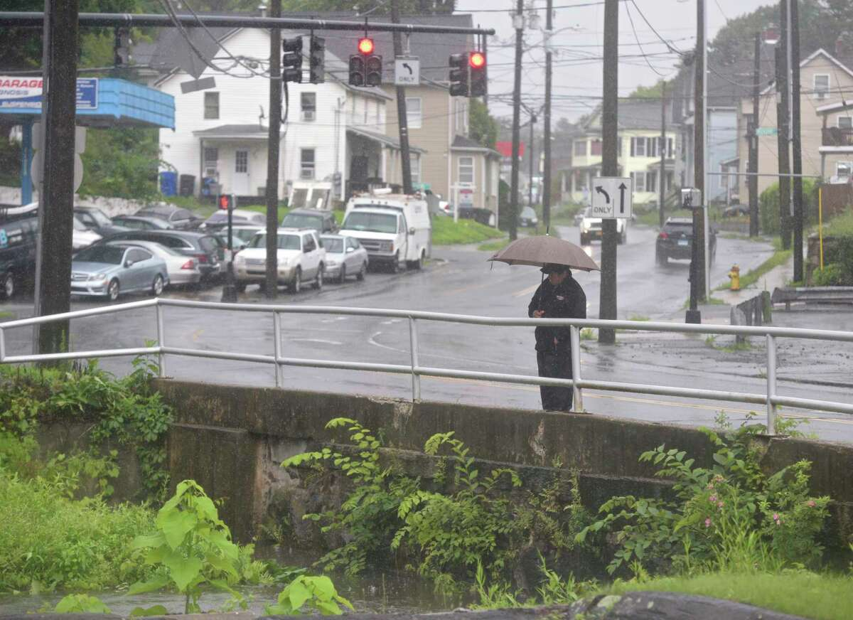 A pedestrian stops to look at the Still River as it passes under West Street. Heavy rains from tropical storm Elsa caused some road flooding in Danbury, Ct, on Friday, July 9, 2021.