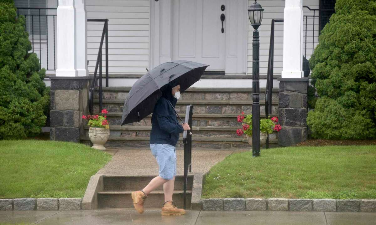 A pedestrian walks along Main Street as heavy rains from tropical storm Elsa caused some road flooding in Danbury, Ct, on Friday, July 9, 2021.