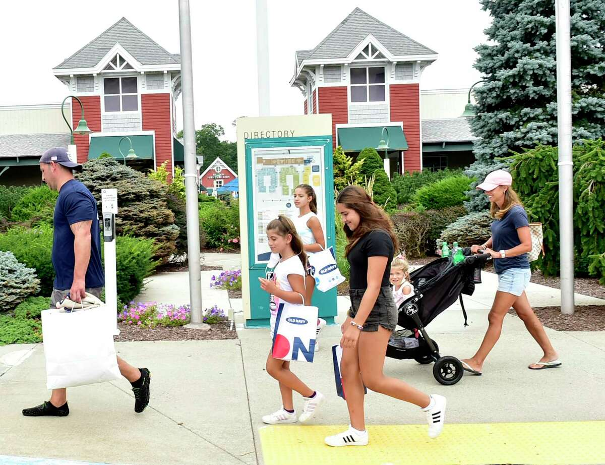Marc and Karen Mirabella of White Plains, N.Y., on vacation in Connecticut, take advantage of the shopping at the Westbrook Outlets Aug. 19, 2021, with their children, from left, Emily, 11, Alexa, 9, Nadia, 3, and Julia, 4.
