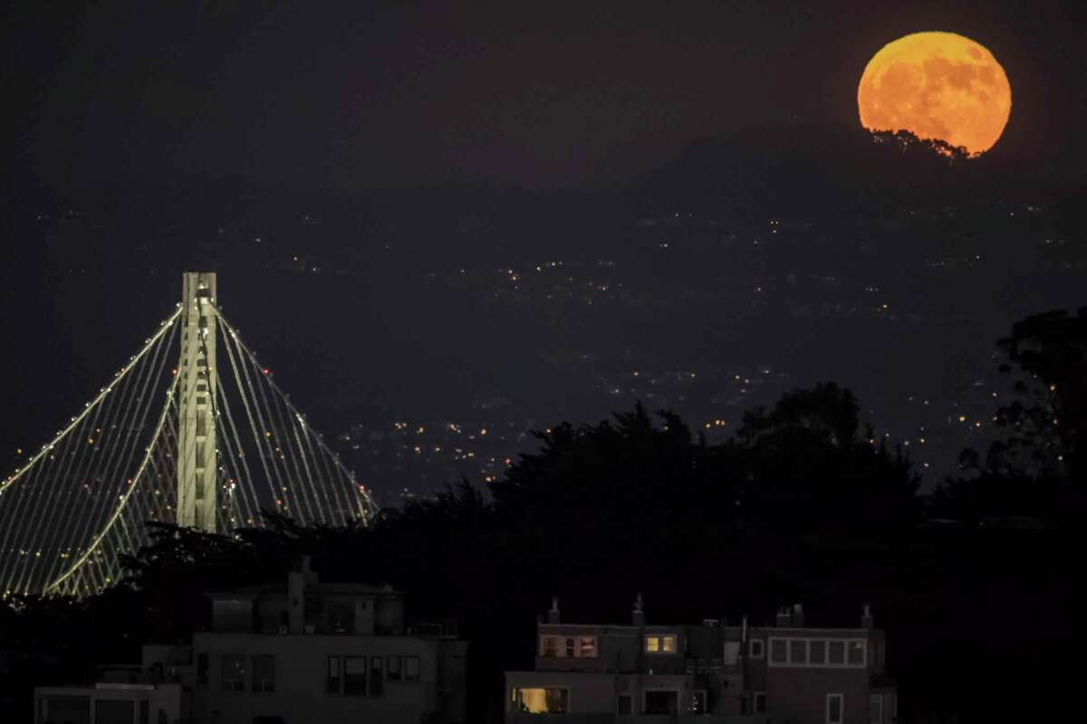 The Halloween blue moon, or second full moon in the month, rises near the eastern span of the Bay Bridge as seen from San Francisco, Calif.