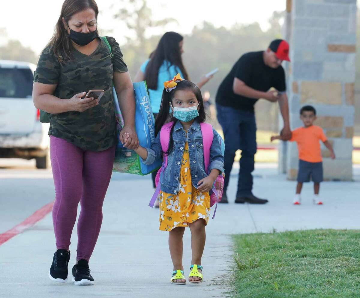 Families wear face masks as they head toward Conroe ISD's new Hope Elementary for the first day of school, Wednesday, Aug. 11, 2021, in Grangerland. The district already has reported more cases of COVID-19 among students and staff than it did all of last year.