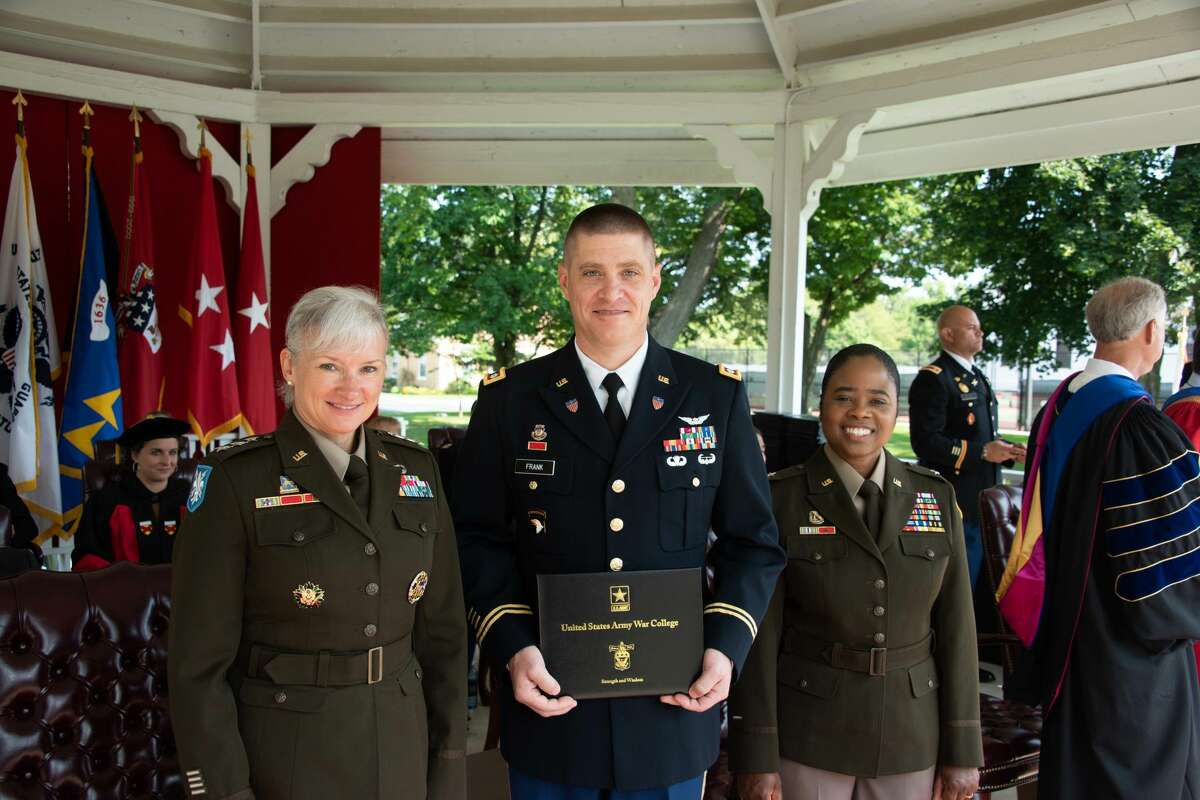 New York Army National Guard Lt. Col. Joseph Frank, center, holds the diploma he earned upon graduation from the Army War College, Carlisle, Pa. He is flanked by Lt. Gen. Laura Potter, left, Army deputy chief of staff for intelligence, Brig. Gen. Janeen Birchead, Army War College deputy commandant for Reserve Affairs.