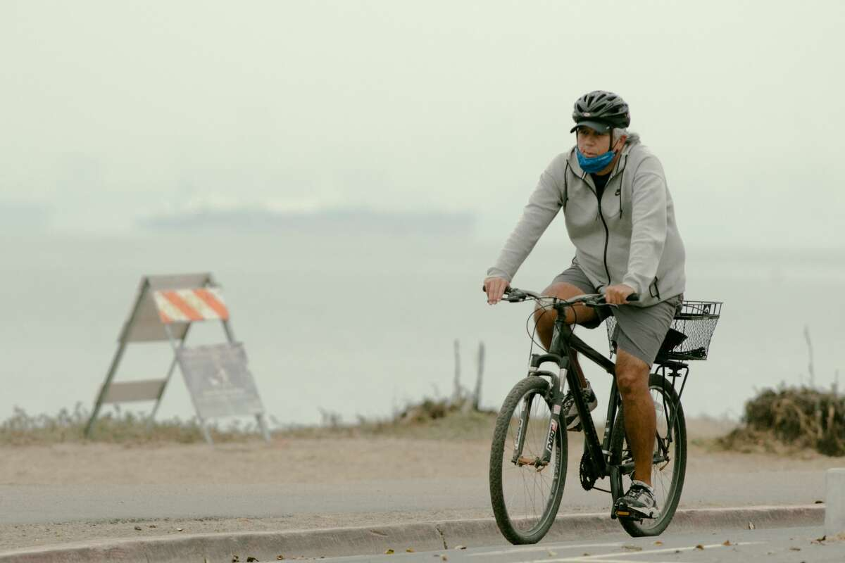 A man rides his bicycle under hazy conditions and poor air quality in Alameda, Calif. on Aug. 20, 2021. Smoke from numerous Northern California wildfires affect air quality throughout the San Francisco Bay Area.