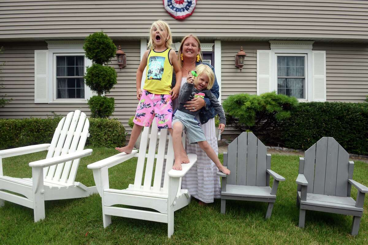 Caraly Schulze poses with her sons Cole and Drew in front of their home in Milford, Conn. Aug. 18, 2021. Schulze is one of the organizers and hosts of PorchFest2021, which will be held in Milford on October 2nd.
