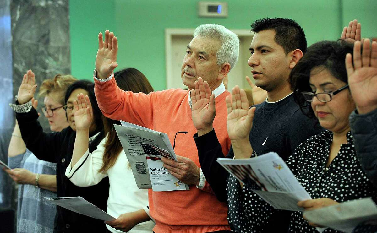 Albino Marinho, 64, center, an immigrant from Portugal, Francisco Gonzalez, 25, and Guadalupe, 50, immigrants from Miexico take the oath of citizenship Wednesday. A naturalization ceremony is held at the Danbury Library Wednesday, April 11, 2018. The share of the Hispanic and Latino population in Danbury grew by 8.2 percentage points over 10 years, one of the largest increases in the state.